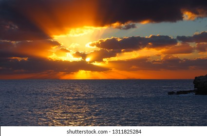 sunset over a calm dark sea with orange rays shining though dark dramatic evening clouds