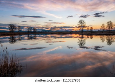 Sunset over calm lake , sky reflection in water in winter.