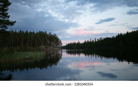 Sunset over a calm lake in sweden, the clouds are reflecting on the calm surface