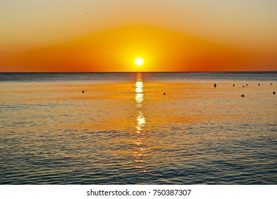 sunset over the Caribbean sea with palm trees and white beaches