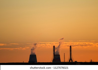 Sunset over the city. CHP pipes, power station. Industrial landscape. Bright sunset over the horizon