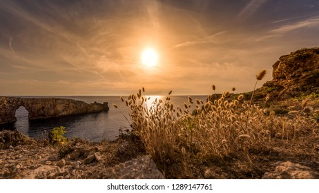 Sunset over the coast of Menorca, looking at Pont d'en Gil, the skin bristles with its colors, we could stay all day in its viewpoint, contemplating the sea and the rocks