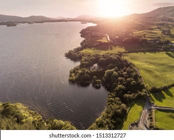 Sunset over Connemara, Lake Corrib, county Galway, warm tones, sun haze. rural landscape.