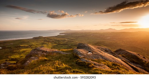 Sunset over Criccieth Bay and the Lleyn Peninsula as seen from the summit of Moel-y-Gest mountain near Porthmadog in the Snowdonia National Park of North Wales.