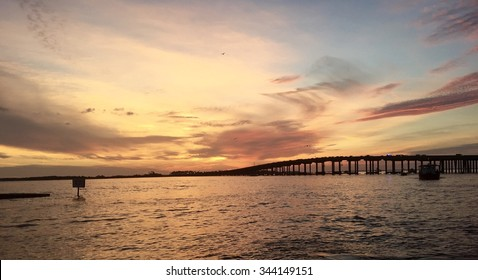 Sunset over Destin bridge during summer taken from the harbor on a dolphin sunset cruise/ Majestic Sunset