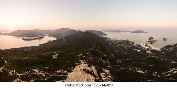 Sunset over Dragon's back hiking trail in Hong Kong island. Aerial panorama with Stanley on the left and Shek O on the right.