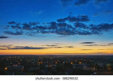 Sunset over evening city, sky with clouds.