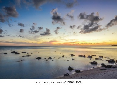 Sunset over a few rocks in the ocean on Eleuthera (Bahamas)
