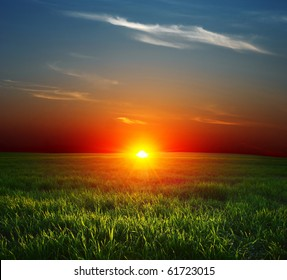 Sunset over field with green grass and sky with clouds