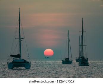 sunset over fishing boat long distance. yatch sailboat without vessel on pole parking on deep sea with colorful twilight evening sky background seascape.