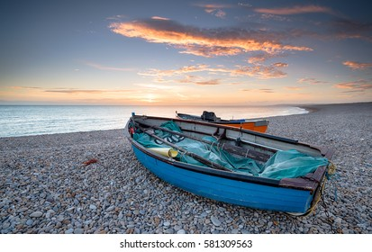 Sunset over fishing boats at Chesil Beach on the isle of Portland near Weymouth in Dorset