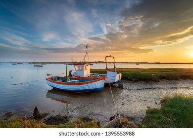 Sunset over fishing boats on the mouth of the River Alde at Aldeburgh on the Suffolk coast