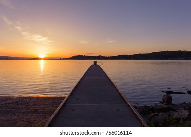 Sunset over Flathead Lake with boat jetty in Wayfarers State Park, Montana, USA
