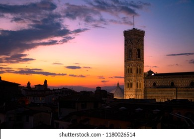 Sunset over Florence rooftops, with the tower of Florence Cathedral (Duomo di Firenze) lit up in the background.