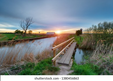 Sunset over a foot bridge leading to Martham Broad on the River Thurne in the Norfolk Broads