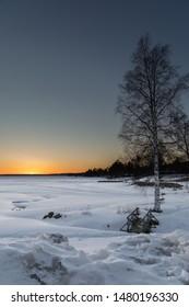 Sunset over frozen lake Siljan in Dalarna, Sweden