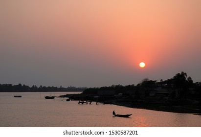 Sunset over the Ganges Delta in Bangladesh. A small boat being paddled on the river and silhouetted against the sun in a pink light. Waterways of the Ganges Delta in southern Bangladesh.