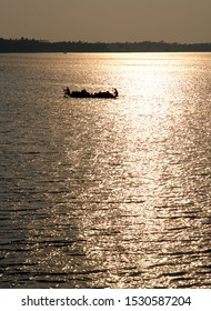 Sunset over the Ganges Delta in Bangladesh. A small boat being paddled on the river and silhouetted against the sun in a golden light. Waterways of the Ganges Delta in southern Bangladesh.