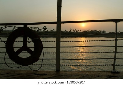 Sunset over the Ganges Delta in Bangladesh. Reflections on the river as seen from the deck of a ship with silhouettes of the railings and trees. Waterways of the Ganges Delta in southern Bangladesh.