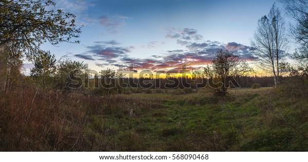 Sunset over the glade. Autumn landscape.