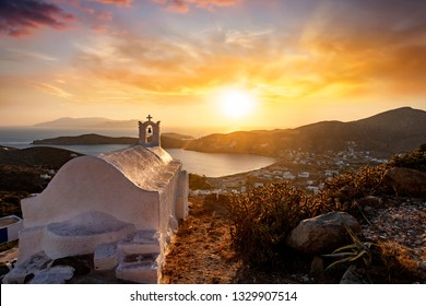 Sunset over the Greek island of Ios with a orthodox church in front on the Cyclades, Greece, during summer time