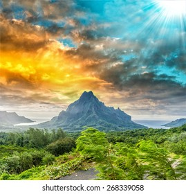 Sunset over green jungle on Rotui mountain with Cook's Bay and Opunohu Bay on the tropical pacific island of Moorea, near Tahiti in French Polynesia