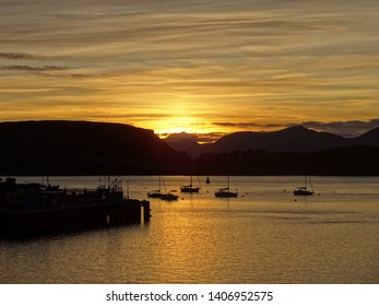 Sunset over the harbour and Oban Bay looking to the Isle  of Mull in Scotland Great Britainwith several sailing boats
