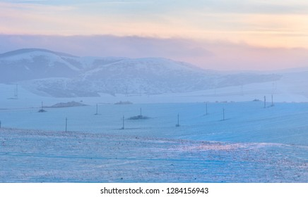 Sunset over hills covered with snow