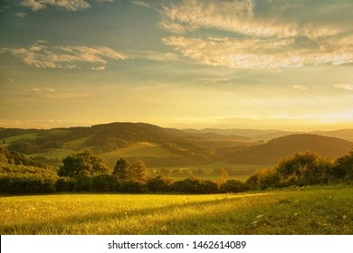 Sunset over hilly landscape, the golden glow of the setting sun, meadow in the foreground
