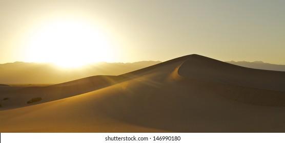 Sunset over the horizon of a desert sand dune.