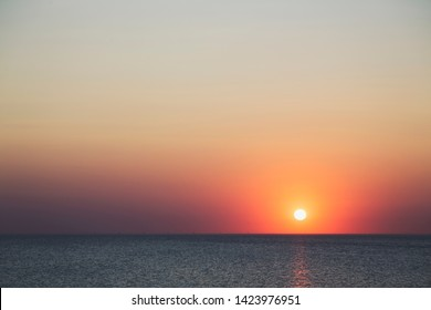 sunset over the horizon of the ocean with cloudless sky