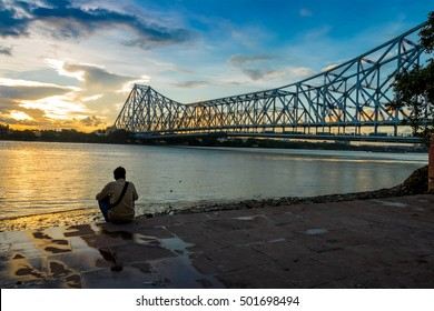 Sunset over the Howrah Bridge on the river Ganges also known as the Hooghly river. Howrah Bridge is a cantilever bridge over the Hooghly River connecting the city of Kolkata with Howrah