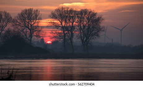 Sunset over an iced lake in the Netherlands with a traditional wind mill and wind turbines on the horizon.
