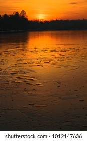 sunset over icy frozen lake