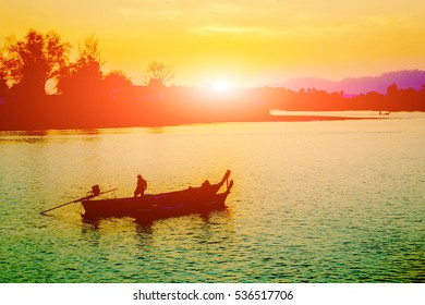 sunset over island at lake with silhouette fisherman works on boat on foreground and sun flare effect background.