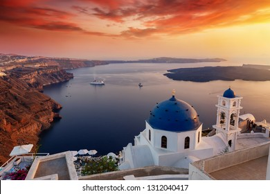 Sunset over the island of Santorini with blue domes of the churches and white houses at the village of Imerovigli, Cyclades, Greece