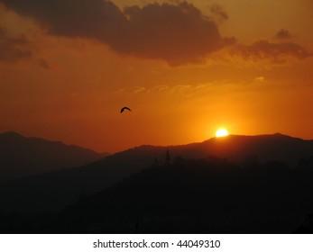 sunset over Kathmandu valley, Nepal, with silhouette of bird and swayambhunath stupa