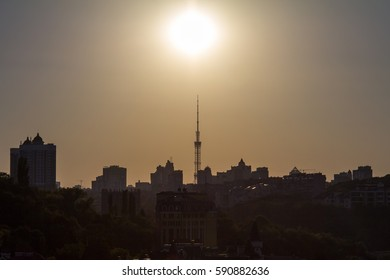 Sunset over the Kiev skyline in Ukraine with skyscrapers and high rise buildings shapes seen into the light