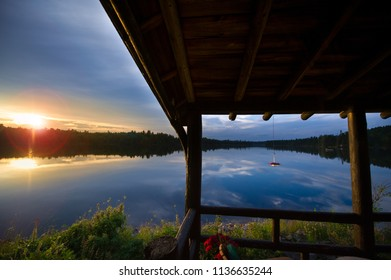 Sunset over a lake in Algonquin Provincial Park, Ontario Canada. Under the porch there's a hummingbird feeder.