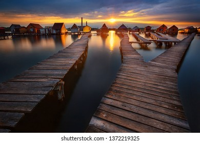 Sunset over lake Bokod with wooden pier and floating houses, power plant in background, Hungary