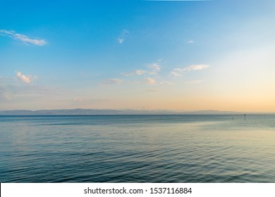 Sunset over lake Constance also called Bodensee in Friedrichshafen. The sky is reflected in the water. The lake is surrounded by three countries: Austria, Swiss, and Germany. The Alps can be seen.