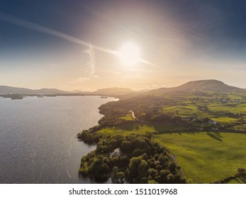 Sunset over lake Corrib and Connemara mountains. Meteorite looking sun and dark blue sky, Haze and warm colors.