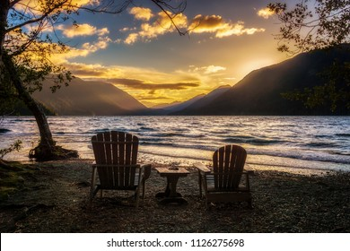 Sunset over Lake Crescent with two wooden chairs on the shore, Olympic National Park, Washington State, USA.