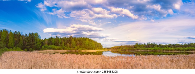 Sunset over lake with forest. Blue sky and clouds. Beautiful scenery in Russia.