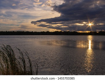 Sunset over lake with sun shining between clouds in start pattern and reflecting on lake. Tall grass in foreground. Sky half covered with clounds.