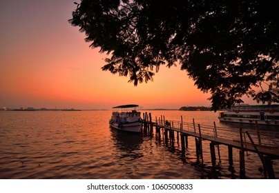 Sunset over lake Vembanad in Marine Drive, Kochi with tourist boats in the background