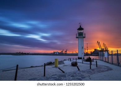 Sunset over the lighthouse at the port