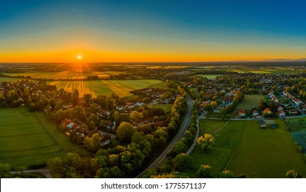 Sunset over a little town, orange sunbeams illuminate the houses. Beautiful time of a springday.