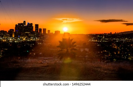 Sunset Over Los Angeles City Skyline - Lights Visible on Buildings