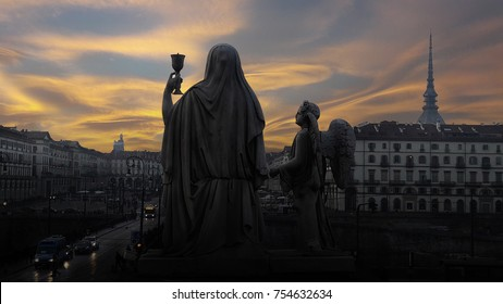 Sunset over the magical Turin. Silhouette of a statue of Faith with a Holy grail in hands and an angel near on a dramatic sky background